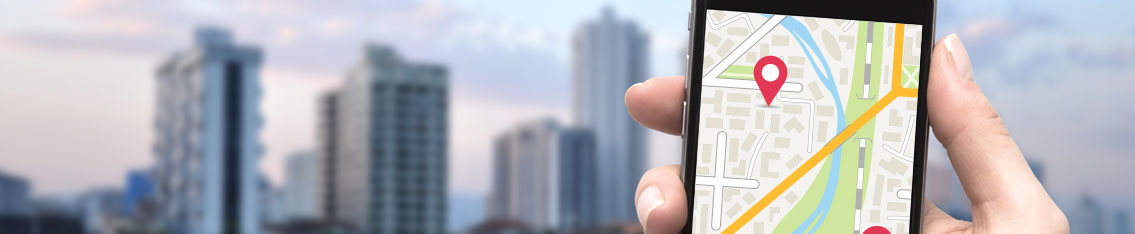 A smartphone with location navigation with cityscape in the background