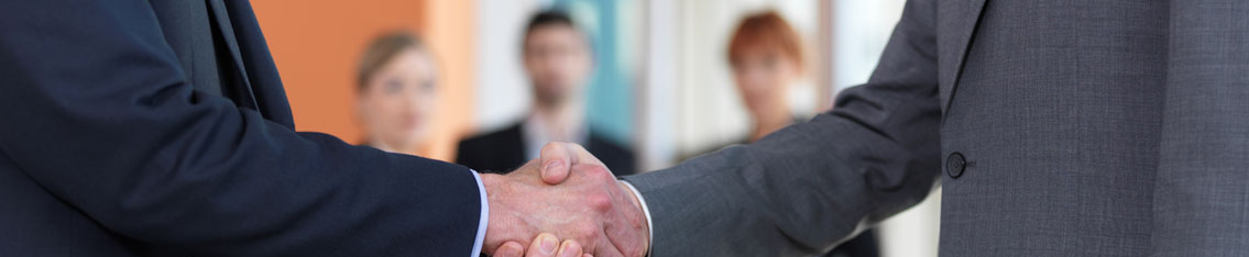 Two business partners shaking hands while staff observe in the background